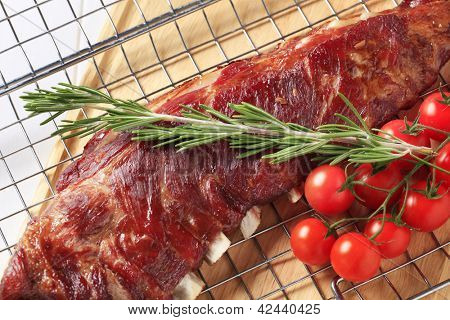 juicy baked ribs with sprig of rosemary and tomatoes