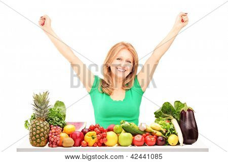 Happy woman with raised hands posing with pile of fruits and vegetables isolated on white background