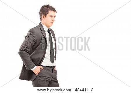 Young professional man with hands in pockets shot during an argue isolated on white background