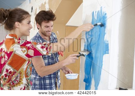 Happy young couple renewing home, painting wall to blue, smiling happy.