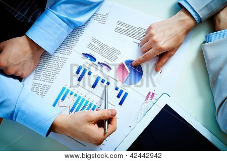Close-up of female and male hands pointing at business document while discussing it