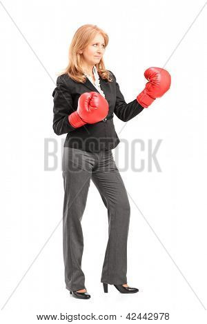 Full length portrait of a mature businesswoman with red boxing gloves ready to fight isolated on white background