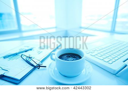 Image of an office workplace with papers, laptop and a cup of coffee