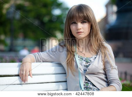 Portrait of a girl. The girl is sitting on a park bench