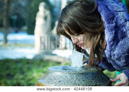 The girl drinks water from a fountain