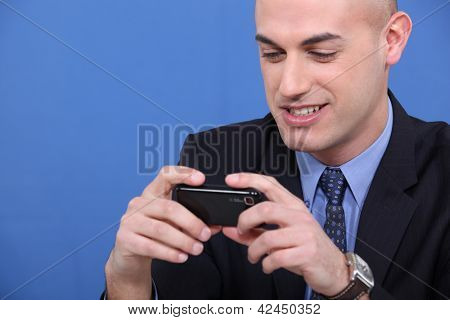 Young bald looking mobile phone screen