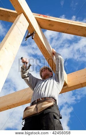 real builder  at work with wooden  roof construction
