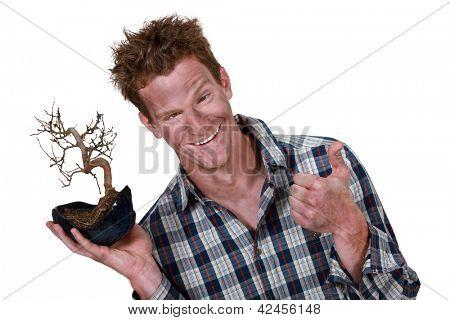 Mann bedeckt mit Staub aufbewahren einer Pflanze-Wurzel und das ein Daumen hoch Zeichen