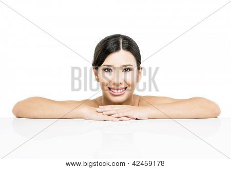 Beautiful Asian woman with arms over a white table