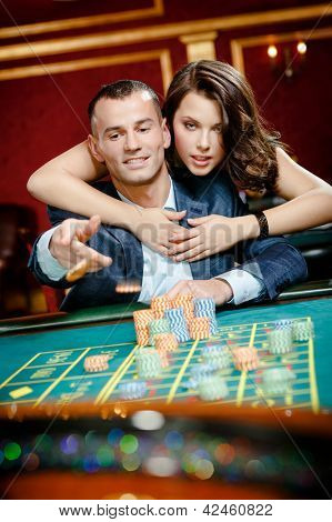 Man embraced by pretty girl throws the chip on the playing table