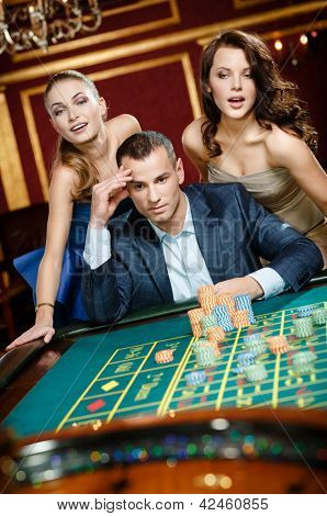 Man with two girls playing roulette at the gambling house. Addiction to the gambling