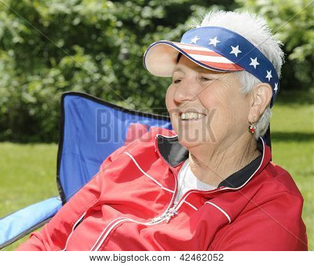 Closeup of a happy senior woman, relaxed and enjoying the sunshine in her casual summer attire.  Her hat has American stars and stripes.