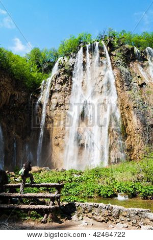 Young Female Tourist Shooting A Waterfal