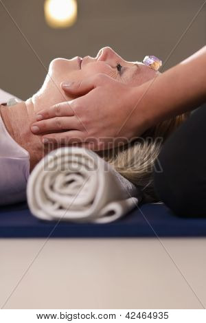 Young Therapist Arranging Crystals On Female Client For Reiki Therapy