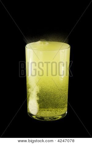 Glasse With Yellow Water And A Tablet.  Isolated On A Black Background