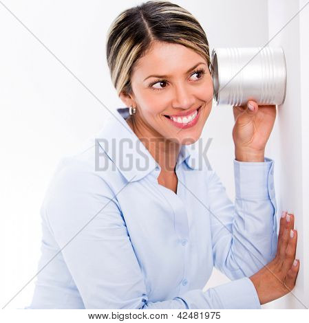 Business woman spying with a glass through a wall