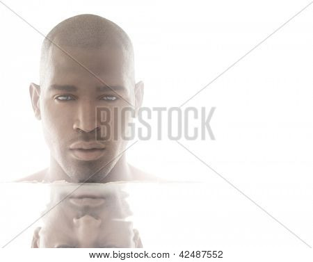 Very lit high-key portrait of a beautiful male model with reflection and lots of copy space against white background