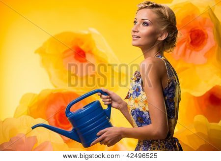 Beautiful dreaming woman in colourful dress with watering can among big yellow flowers