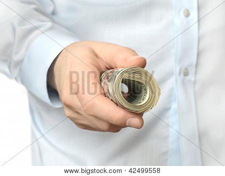 Roll of dollar bills in hand