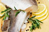 stock photo of hake  - Arrangement of Fillet Raw Fish Hake Lemon and Rosemary with Black Peppercorn closeup on Cutting Board - JPG