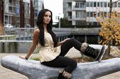 image of mukluk  - woman sitting on curvy carved stone bench - JPG
