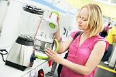 stock photo of mixer  - Young woman choosing kitchen mixer blender in home appliance shopping mall supermarket - JPG