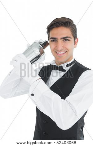 Attractive young barkeeper shaking a drink smiling at camera