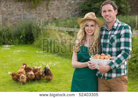 Young couple holding a basket filled with eggs in their garden with chickens behind