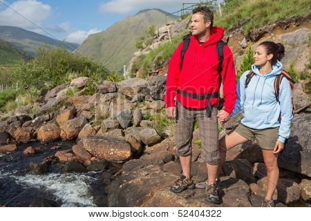 Couple standing at edge of river on a hike in the countryside