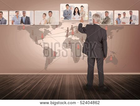 Businessman selecting digital interface showing business people with map on background
