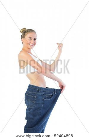 Confident triumphant blonde wearing too big trousers on white background