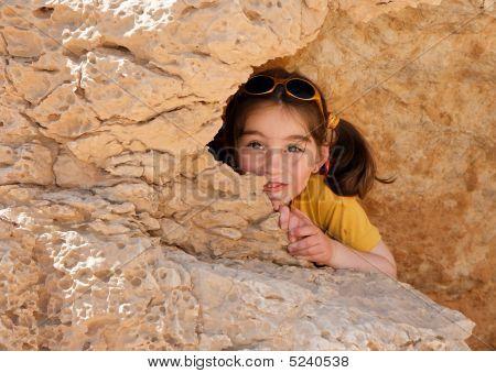 Niña linda oculta detrás de una roca