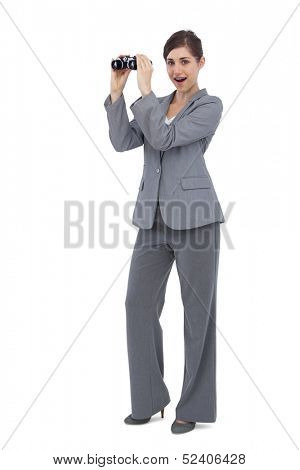 Astonished businesswoman on white background posing with binoculars