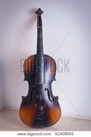 old violin leaning against the wall