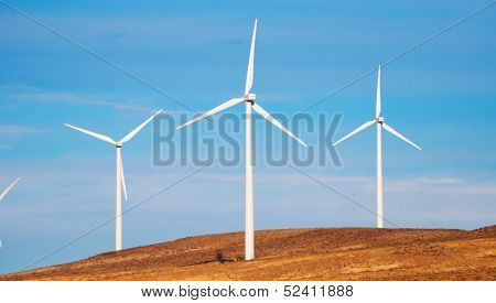 Wind Turbines on a Grassy Knoll with Blue Sky