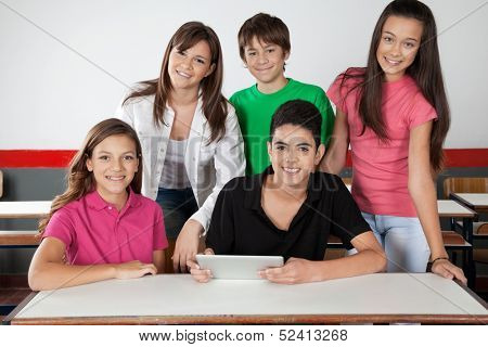 Portrait of teenage school students using digital tablet at desk in classroom