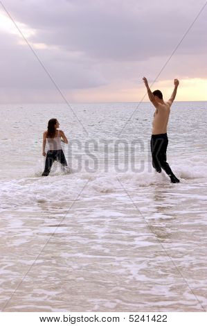 Couple Playing In The Ocean With Clothes On