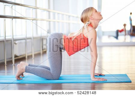 Portrait of happy young woman doing exercise for back in gym