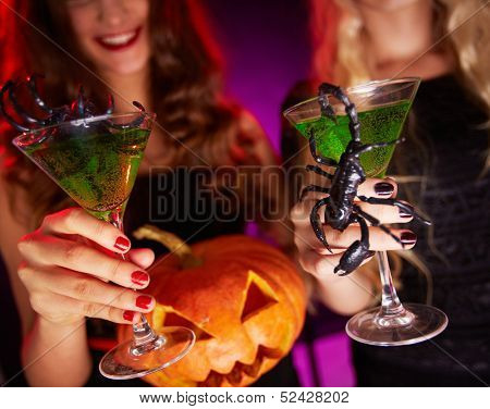 Photo of carved Halloween pumpkin and cocktails with scorpions held by females