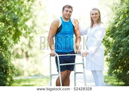 Pretty nurse and male patient looking at camera in park