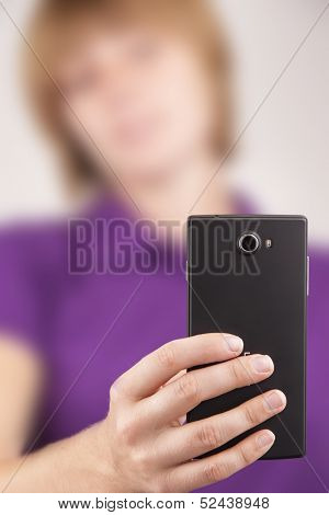 Young woman taking a photo with her smart phone