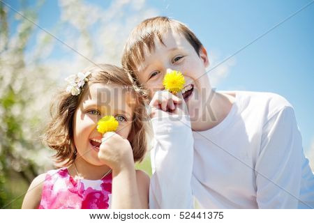 Happy children wearing clown noses looking down on the camera. Playful noses from a dandelions