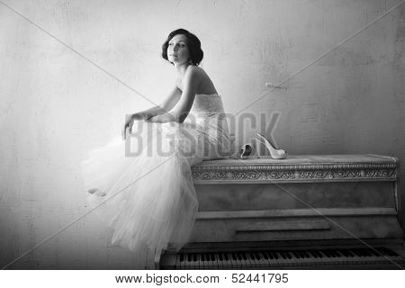 Beautiful young woman sitting on a white piano. Retro style