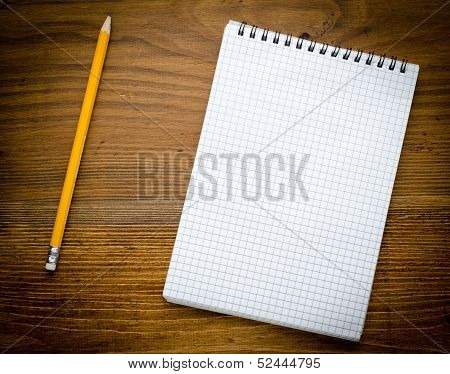Black notebook with pencile on a wood background