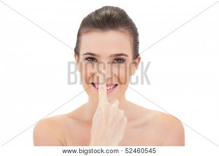 Amused natural brown haired model touching her nose on white background