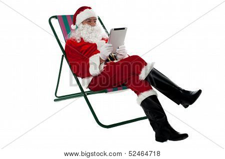 Kris Kringle Relaxing And Using Electronic Tablet