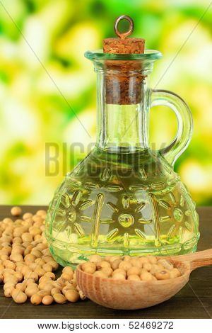 Soy beans and oil on table on bright background
