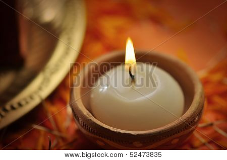 A close up of a candle in an earthen candle-holder