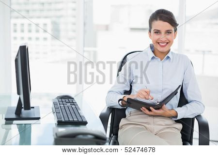 Pleased classy brown haired businesswoman checking her agenda in bright office