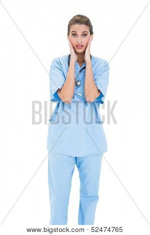 Astonished brown haired nurse in blue scrubs posing with head in hands on white background